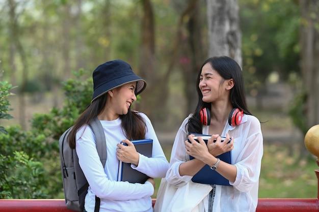 Два счастливых студента колледжа разговаривают и смеются друг с другом, стоя в парке в кампусе