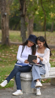 Два счастливых студента колледжа смотрят что-то на цифровом планшете и сидят вместе в кампусе