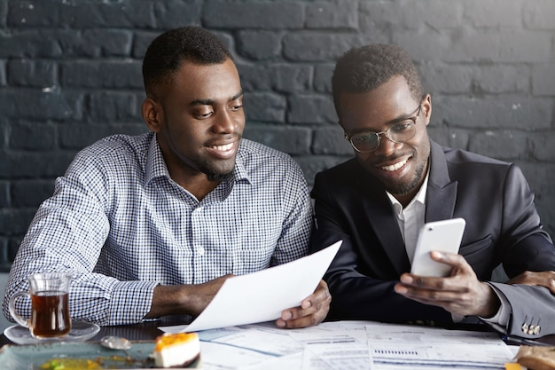 Two happy confident dark-skinned colleagues surfing internet on mobile phone while having break