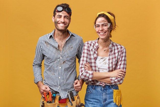 Два счастливых, уверенных в себе ремонтника в защитной одежде, стоящие рядом друг с другом у глухой стены и широко улыбающиеся, готовые к ремонту, починке и ремонту