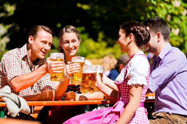 Two happy couples sitting in beer garden