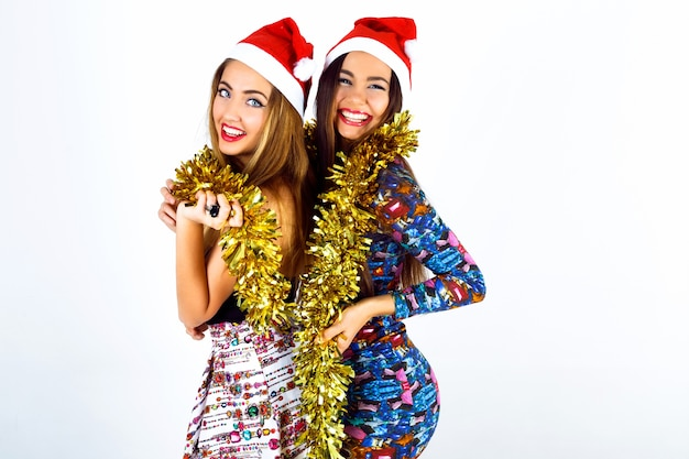 Two happy crazy best friends girls ready for celebrating new year party, holding tinsel screaming