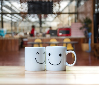Two happy cups on coffee store blur background, valentine and business concept