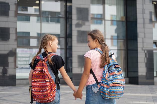배낭과 책을 든 두 명의 행복한 백인 소녀가 학교에 가서 함께 이야기합니다. 보기 드문 보기. 학교 개념으로 돌아가기.