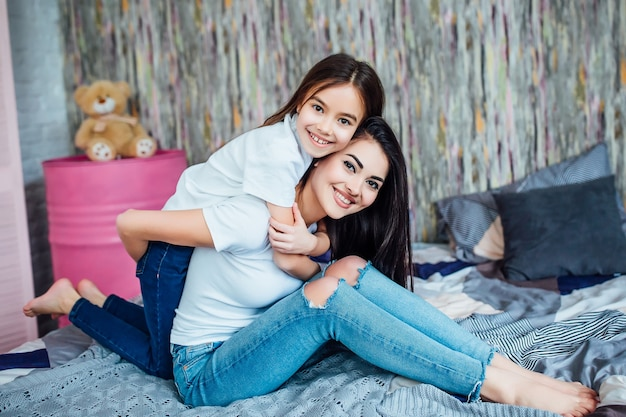Two happy cute sisters lying on bed in bedroom at home and playing