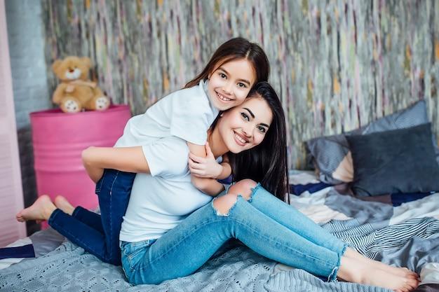 두 명의 행복한 귀여운 자매가 집에서 침실에 누워 놀고 있다