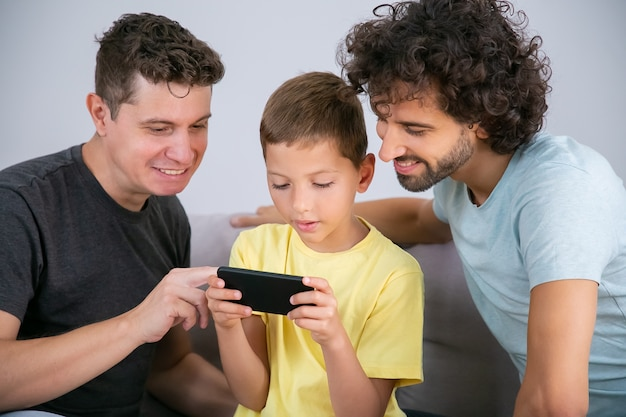 Due papà felici che insegnano al figlio a usare l'app online sul cellulare. ragazzo che gioca gioco sul telefono cellulare. famiglia a casa e concetto di comunicazione
