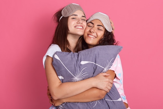 Two happy dark haired female wearing pajamas and blindfolds, hugging and embracing pillow, keeping eyes closed, expressing happiness, enjoying spending time together.