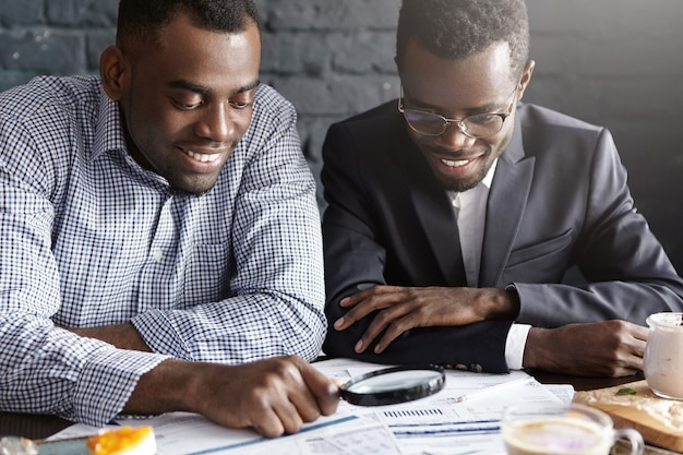 Two happy dark-skinned businessmen reading documents with magnifying glass