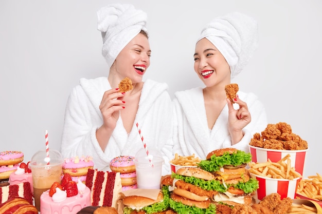 Two happy diverse women look gladfully at each other hold nuggets eat tasty fast food
