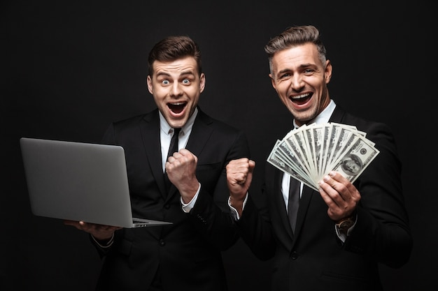 Two happy excited businessmen wearing suits standing isolated over black wall, holding laptop computer, showing money banknotes