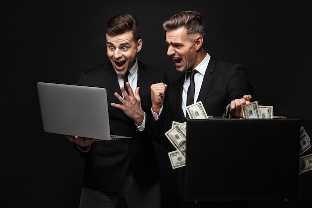 Два счастливых возбужденных бизнесмена в костюмах, стоящих изолированно над черной стеной, держат портативный компьютер и демонстрируют портфель, полный денежных банкнот