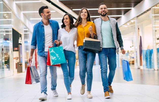 쇼핑 가방과 함께 두 행복 흥분된 커플은 함께 시간을 보내고 재미 쇼핑몰에서 걷고있다