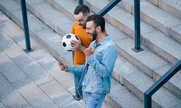 야외에서 손에 스마트 폰으로 내기에서 승리 한 후 행복감에 두 명의 행복 흥분된 팬 친구