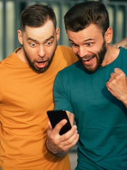손에 스마트 폰을 들고 내기에서 승리 한 후 행복감에 두 명의 행복한 흥분된 팬 친구