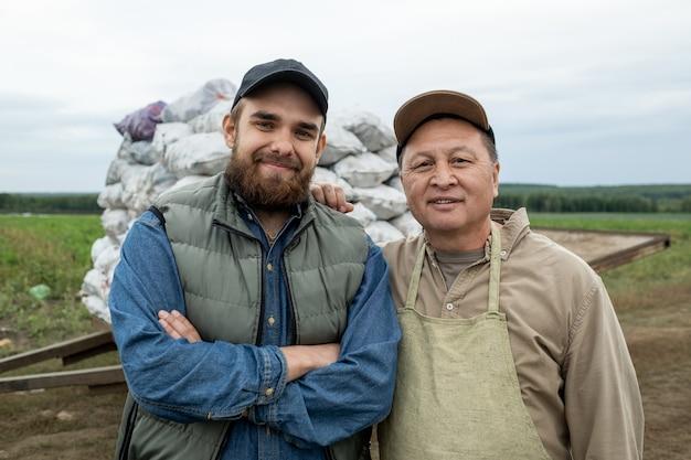 Два счастливых фермера в спецодежде стоят против кучи мешков с картофелем