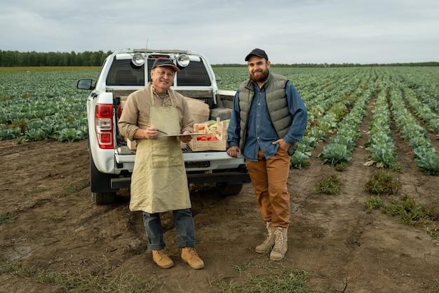 Два счастливых фермера в спецодежде стоят у багажника машины