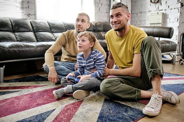 Два счастливых отца поддерживают своего маленького сына, играющего в видеоигру на консоли
