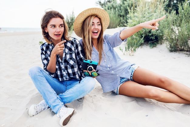 Две счастливые подруги веселятся на пляже