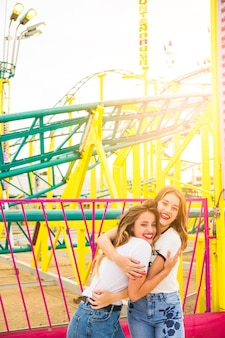 Two happy female friends hugging each other in front of roller coaster ride