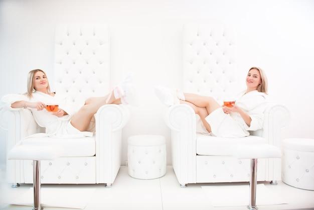 スパサロンの白いホールでフルーツ ティーを使ってペディキュアした後、白いバスローブを着た 2 人の幸せな女性の友人。