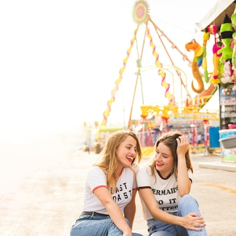 Two happy female friends sitting on pavement at amusement park