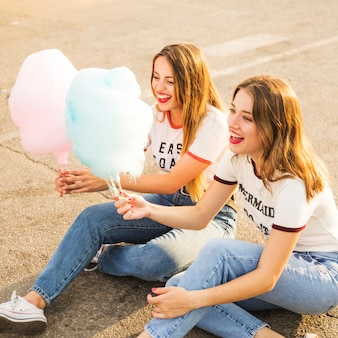 Two happy female friends sitting on street holding candy floss