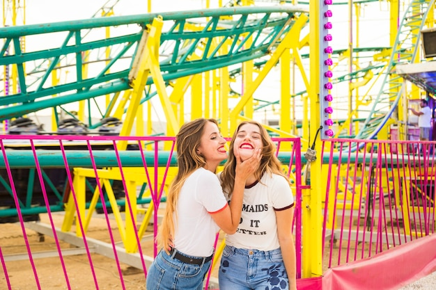 Two happy female friends standing in front of roller coaster ride