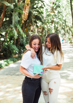 Two happy female friends with gift box standing in park