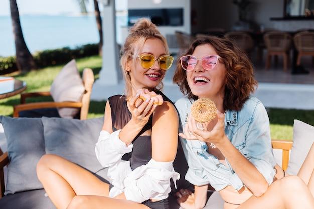 분홍색과 노란색 선글라스에 두 행복 맞는 여자 재미 도넛, 야외와 함께 웃고 웃고