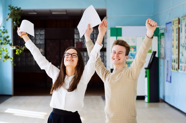Two happy friends after researching their checked exams