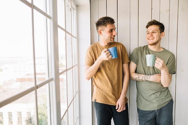 Two happy friends drinking morning coffee standing near window