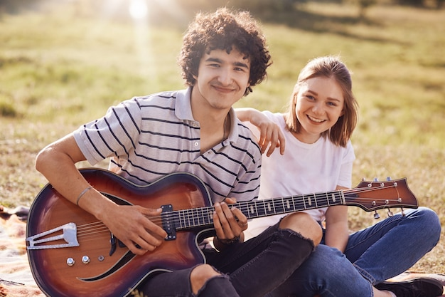 Two happy friends have joyful expression, gentle smiles on faces, during summer time outdoor, play guitar and sing popular songs, can`t imagine their lives without music. rest concept