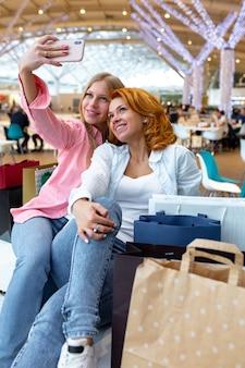 ショッピングモールで買い物をしながら2人の幸せな友達が自分撮りをしています