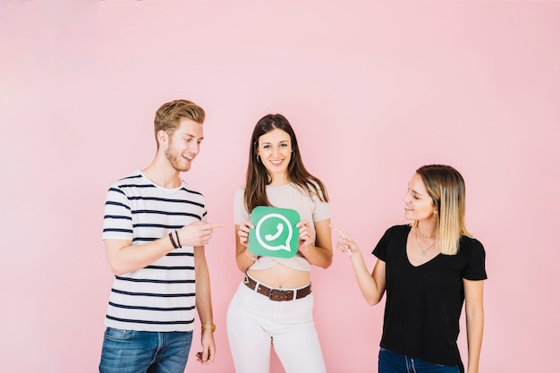Two happy friends pointing at woman holding whatsapp icon