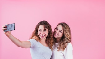 Two happy friends taking self portrait on cellphone standing against pink backdrop