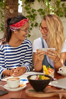 Two happy friends watch video on mobile phone, have coffee break after classes, wear spectacles, eat delicious salad and drink coffee, pose against cozy cafe interior, connected to wireless internet