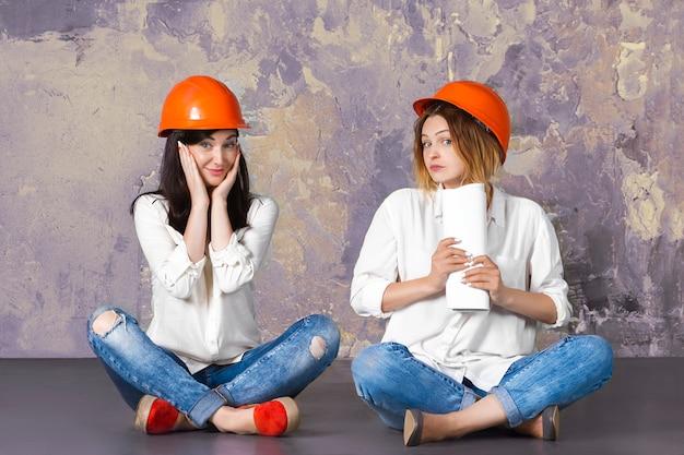 建築図面と下書きで床に座ってヘルメットを構築オレンジ建設保護の2つの幸せな面白いかわいい建築家女性女性少女。