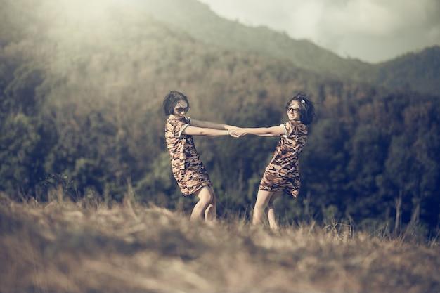 2人の幸せな面白い姉妹双子かわいい子供は夕日の光線フィールドバックのサマーパークで楽しんでいます