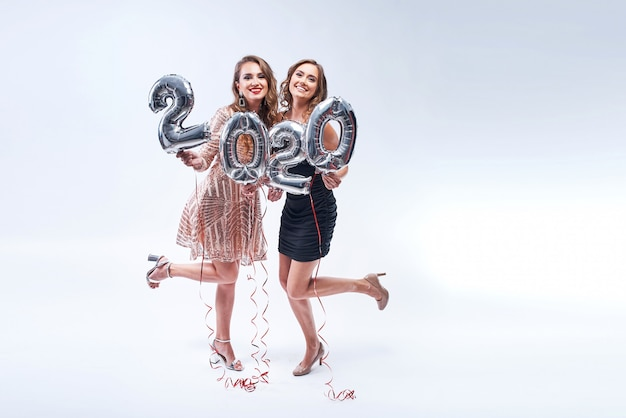 Two happy girl friends with metallic 2020 balloons on white .
