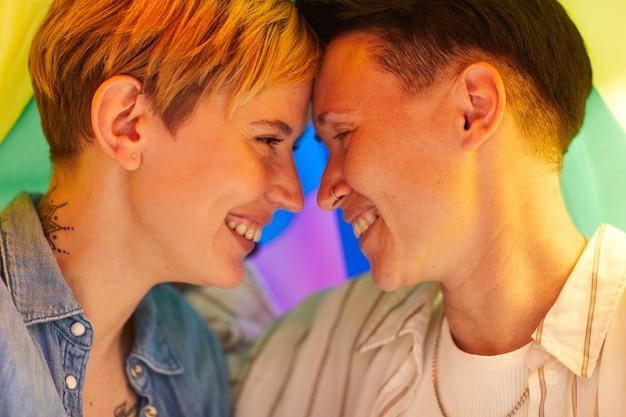 お互いを見て、色の旗の下で笑っている2人の幸せなガールフレンド