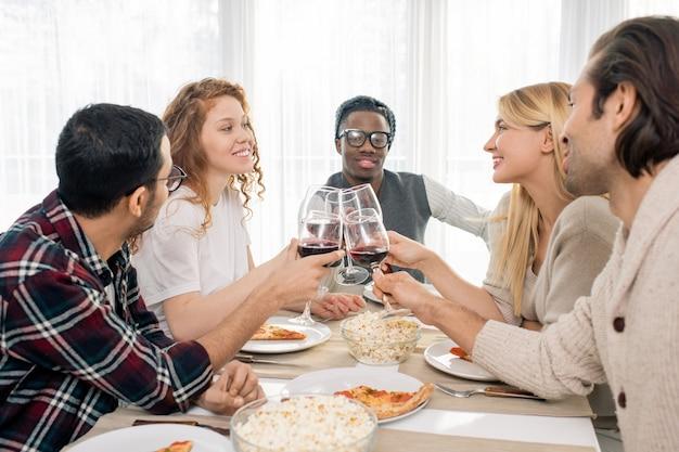 Две счастливые девушки и трое межкультурных парней чокаются бокалами красного вина за праздничным столом к обеду
