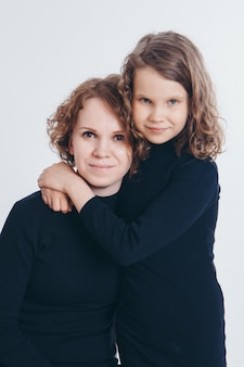 Two happy girls are smiling. portrait of a mother and daughter embracing. the concept of family relations, friends, family day, mother's day