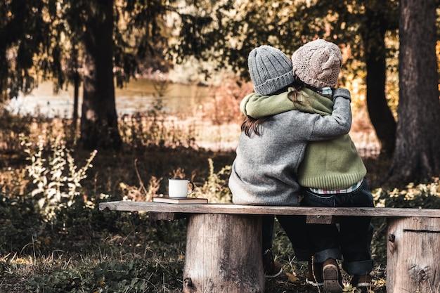 友達として2人の幸せな女の子がお互いを抱きしめます。公園の小さなガールフレンド。子供の友情。