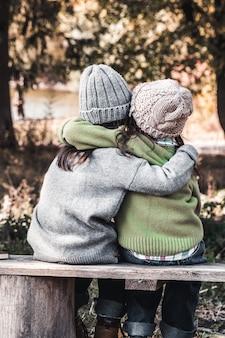 Две счастливые девушки как друзья обнимают друг друга. маленькие подруги в парке. детская дружба.