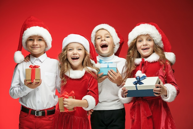 Two happy girls and boys in santa claus hats with gift boxes at red studio