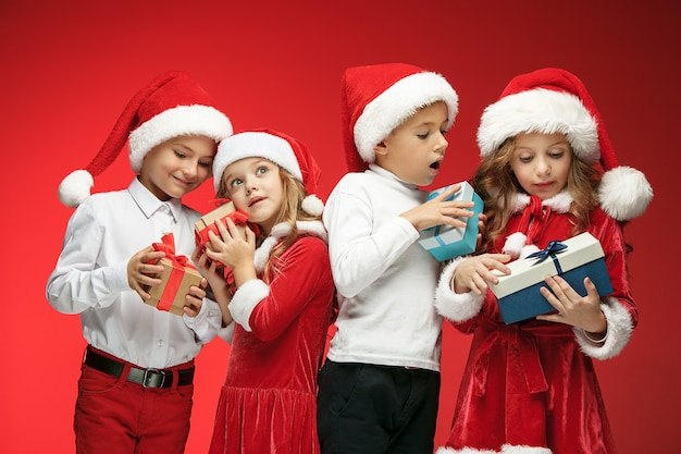 Two happy girls and boys in santa claus hats with gift boxes on red