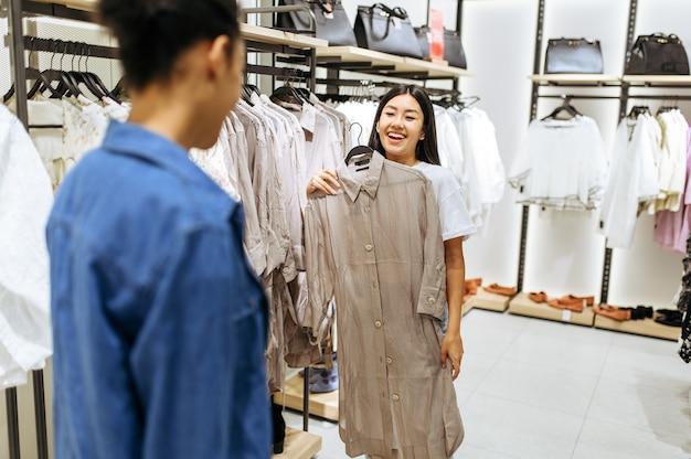 衣料品店で服を選ぶ2人の幸せな女の子