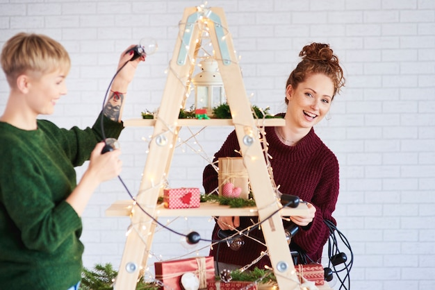 Two happy girls decorating the christmas tree