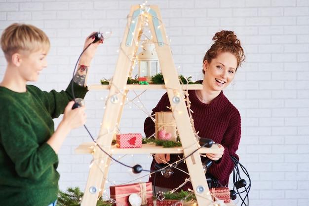 크리스마스 트리를 장식하는 두 행복 한 여자